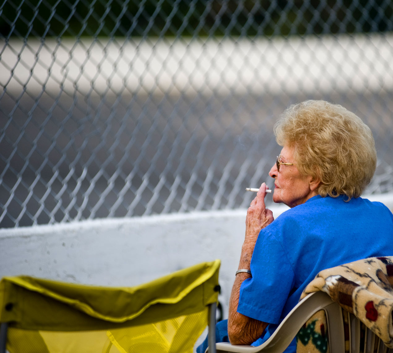 Women smokes and watches nascar at Wake County Speedway